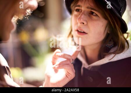 emotional woman with raised chin looking at laughing counterpart at night, nightlife in city Berlin, Germany - Stock Photo