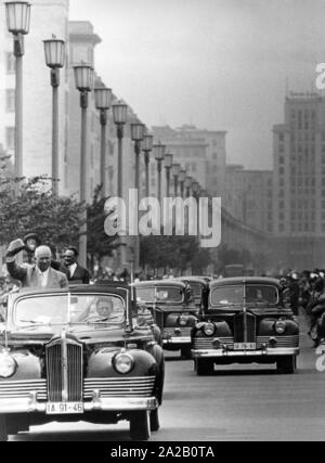 Nikita Sergeyevich Khrushchev, party leader of the CPSU, and Anastas Mikoyan, deputy Prime Minister, are driven through East Berlin in open limousines. The picture shows them during their ride through the Stalin Allee, on the roadside stand the cheering people. Khrushchev and his delegation visited the GDR between 07.08.1957 and 14.08.1957. The cars are ZIS-110 parade cars, which were also available as convertibles. - Stock Photo