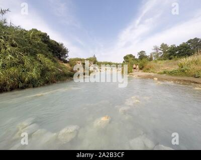 Saturnia, Italy - July, 2019: Natural spa with waterfalls in Saturnia, Tuscany, Italy. - Stock Photo