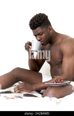 man with breakfast, grapes and coffee, reading newspaper in bed, getting up, in Munich, Germany - Stock Photo