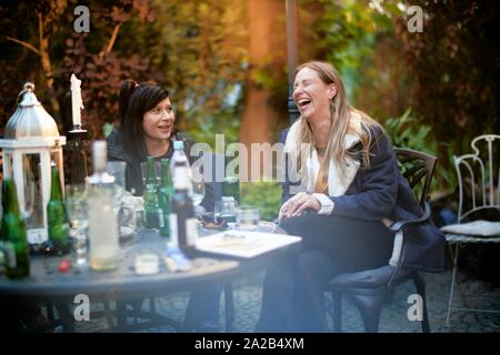 happy middle-aged woman laughing at garden party with friend