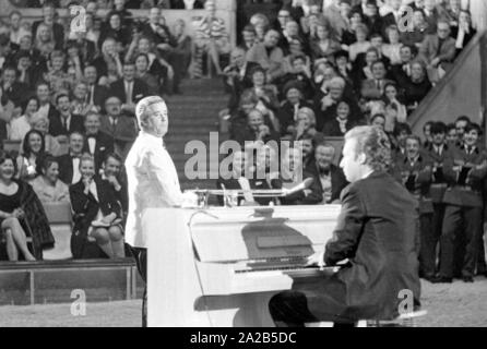 A circus program was held annually by celebrities in front of an audience for the television show 'Die Goldene Zehn' at Circus Krone in Munich. Photo of Peter Alexander at the piano. - Stock Photo