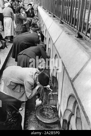 In the holy district of the pilgrimage destination of Lourdes, believers drink from the water which they believe to have miraculous healing power (undated photo). - Stock Photo