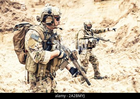 Two armed US army commandos or military scouts equipped with radio headset moving forward in sands during enemy area reconnaissance. Special forces - Stock Photo