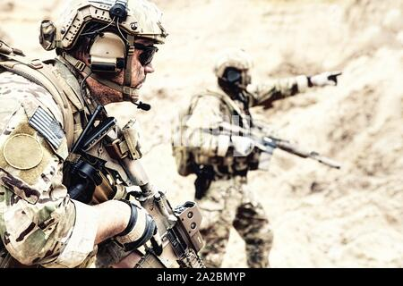 US special operations forces fighters armed with assault rifle, in opscore helmet, radio tactical ops headset, moving forward with caution in desert. - Stock Photo