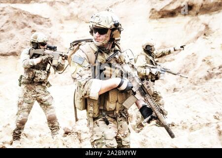 Group of well equipped US army commandos armed with assault rifles, moving through sandy terrain or desert. Military reconnaissance team secret - Stock Photo