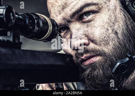 Army sniper with bearded, dirty face aiming with optical telescopic sight on sniper rifle, observing battlefield from ambush and searching targets to - Stock Photo