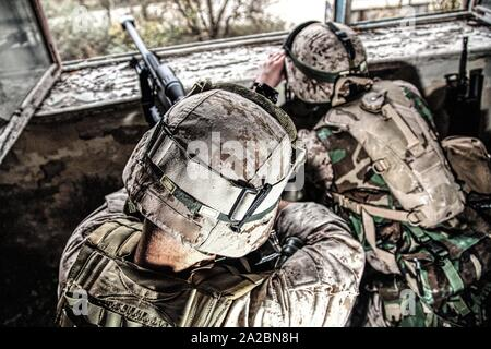 Marines sniper team armed with large caliber, anti-materiel sniper rifle hiding in ruined urban building, shooting enemy targets on range from - Stock Photo