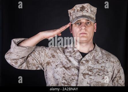 Shoulder portrait of saluting United States Marine Corps infantry in camo uniform and eight-pointed utility cap or cover with USMC Eagle, Globe, and