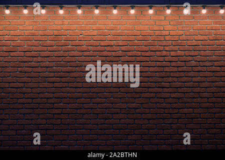 An orange brick wall with small light bulbs. Gradient stone background with low light and copy space. Place for advert. - Stock Photo