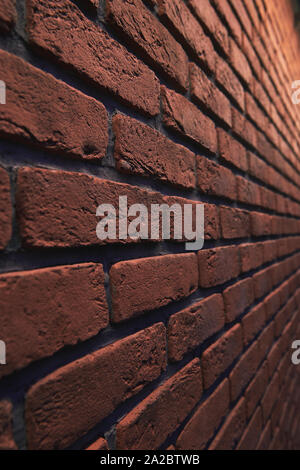 An orange brick wall at an angle with bokeh. Stone blurred background. Closeup. Vertical photo. - Stock Photo