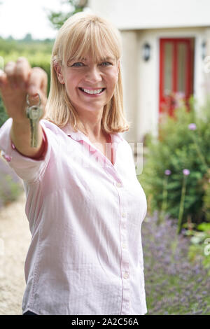 Portrait Of Mature Woman Standing In Garden In Front Of Dream Home In Countryside Holding Keys - Stock Photo