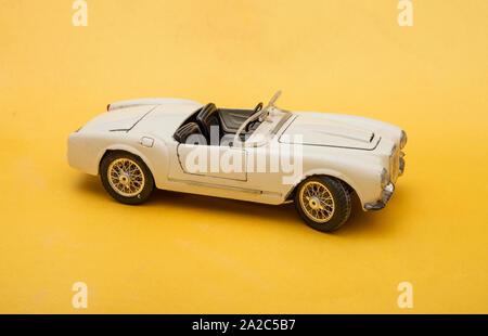 White retro car toy model isolated on yellow background, transportation concept - Stock Photo