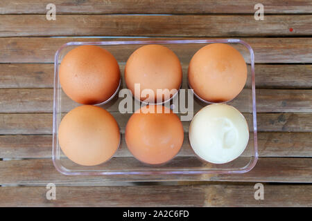 close up Six brown eggs in plastic box on bamboo table with one broken boiled egg, top view. - Stock Photo