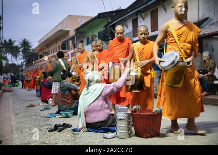 Tak bat Monks call to alms at dawn, Luang Prabang, Luang Prabang province, Northern Laos, Laos, Southeast Asia Stock Photo