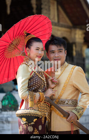 Young couple posing for wedding photo in traditional dress outside Wat Xiengthong, Luang Prabang, Luang Prabang province, Northern Laos, Laos, Southea - Stock Photo