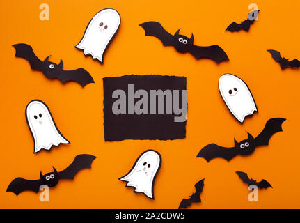 Terrifying Halloween flat lay on orange background with bats and ghosts - Stock Photo