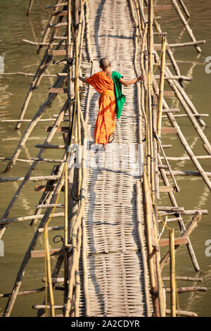 Young Buddhist monk crossing the bamboo footbridge over the Nam Khan River, Luang Prabang, Luang Prabang province, Northern Laos, Laos, Southeast Asia Stock Photo