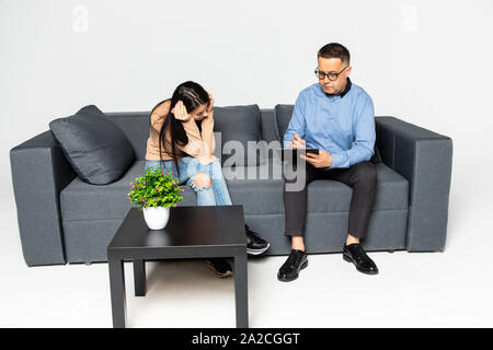 Beautiful woman in casual clothes is sitting on the couch at the psychotherapist. Handsome middle aged doctor is holding a folder and talking to her - Stock Photo