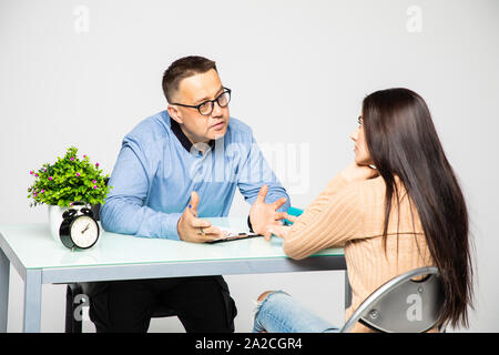 Sad attractive woman talking to psychotherapist during therapy - Stock Photo