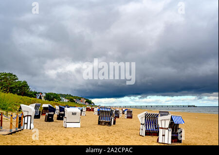 Bansin, Germany - September 13, 2019: Lonely beach with beach chairs on Usedom overlooking the sea to dramatic looking storm clouds. - Stock Photo