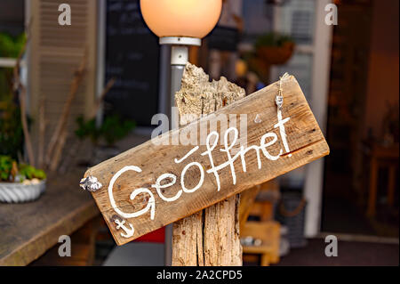 Board on a wooden post in front of a shop with the word 'geoeffnet' - that's German for 'open'. - Stock Photo