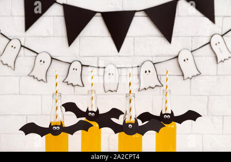 Assortment of Halloween yellow drinks with paper bats - Stock Photo