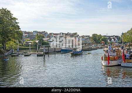 Traditional boats outside Teddington Lock, London, UK during the Great River Race 2019 with people/crew watching rowing crew leave lock. - Stock Photo