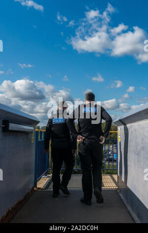 Two male British Transport Police officers in uniform crossing public footbridge from behind. Rear view two men sunny with blue sky - Stock Photo