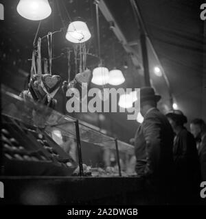Kundschaft am Süßwarenstand auf der Festwiese in Berlin Stralau, Deutschland 1930er Jahre. Customers at the candy booth at the Berlin Stralau annual fair, Germany 1930s. - Stock Photo