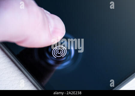 Unlocking the phone with the finger on a digital fingerprint scanner built in under the screen close up - Stock Photo