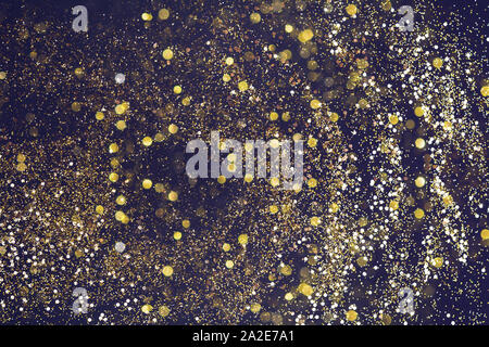 Golden glitter scattered on the dark card background, top view. Abstract pattern created by hand, imitaion of storm, beautiful bokeh, selective focus - Stock Photo
