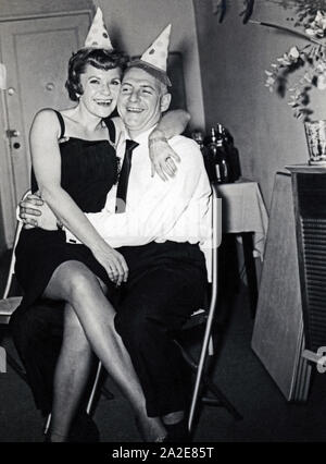 Couple celebrating the New Year at home, circa 1950s, USA. - Stock Photo