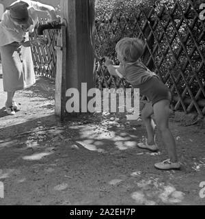Ein kleiner Junge pumpt Trinkwasser aus einem Brunnen, Deutschland 1930er Jahre. A little boy pumping up water for his mother, Germany 1930s. - Stock Photo