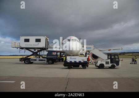 An EasyJet Airbus A319-111 parked on the concrete apron surrounded by various service vehicles at Inverness Dalcross Airport, Scottish Highlands, UK. - Stock Photo