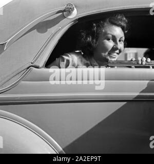 Eine junge Frau schaut aus dem Fenster eines abgedeckten Cabrio Ford V8, Deutschland 1930er Jahre. A young female looking out of the window of a closed convertible Ford V8, Germany 1930s. - Stock Photo