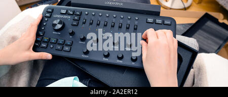 Paris, France - Spe 13, 2019: overhead view of female video editor vlogger retoucher woman holding unboxing operating new Loupedeck Plus photo and video editing console - Stock Photo