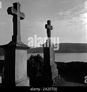 Grabkreuze auf dem Friedhof mit Blick auf das Totenmaar in Weinfeld bei Daun in der Eifel, Deutschland 1930er Jahre. Tombstones with view to Totenmaar maar lake at Weinfeld near Daun at Eifel region, Germany 1930s.