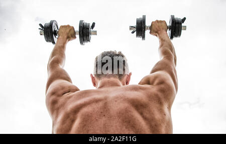 Sport equipment. Bodybuilding sport. Sport lifestyle. Dumbbell exercise gym. Muscular man exercising with dumbbell rear view. Pain is temporary, pride - Stock Photo