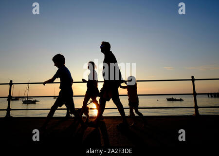 A family in silhouette on holiday walking along the revetment promenade with their dog at sunset in Totland Bay on the Isle of Wight - Stock Photo