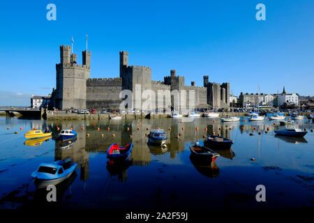 View across the River Sieont toward Caernarfon castle on a still calm morning reflecting on the water at high tide with moored boats in the foreground - Stock Photo