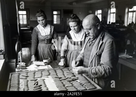 Der Besitzer einer Zigarrenfabrik bei Marburg erklärt seinen in Marburger Tracht gekleideten Mitarbeiterinnen die Qualitätskontrolle der fertigen handgerollten Zigarren, Deutschland 1930er Jahre. The owner of a cigar company near Marburg is explaing the quality check of the finished hand-rolled cigars to his female cigar rollers who are wearing a Marburg garb / costume, Germany 1930s. - Stock Photo