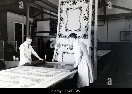 Zwei Mitarbeiter einer Textilfirma in Krefeld bedrucken eine Stofbahn mit einem Blumenmuster durch das Siebdruckverfahren, Deutschland 1930er Jahre. Two employees of a textile company in Krefeld silk-screening a flower pattern on a panel, Germany 1930s. - Stock Photo
