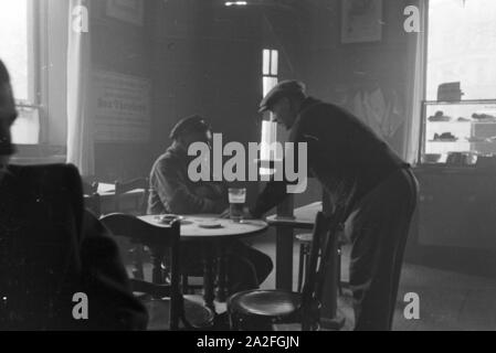 Zwei Mitarbeiter einer Druckerei, die mit Geräten der Firma MAN arbeitet, bei einem Feierabendgetränk in der Kantine, Deutschland 1930er Jahre. Two employees of a printery, that is using devices produced by the enterprise MAN, having an after-work drink in the canteen, Germany 1930s. - Stock Photo