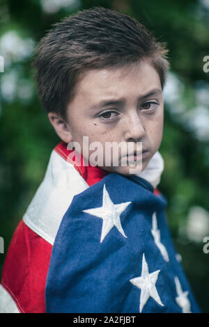 Little mixed race Asian Caucasian brunette boy wrapped in American flag with serious sad expression frown - Stock Photo