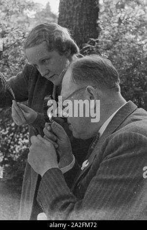 Ein Mann und eine Frau prüfen einen Schmalfilm, Deutschland 1930er Jahre. A man and a woman checking a substandard film, Germany 1930s. - Stock Photo