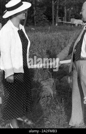 Ein Mann und eine Frau in einem Garten, Deutschland 1930er Jahre. A man with a woman in a garden, Germany 1930s. - Stock Photo