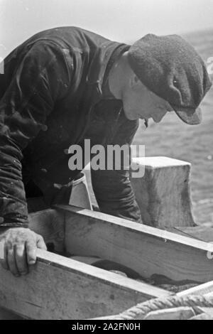 Ein Hochseefischer bei der Arbeit an Deck, Deutschland 1930er Jahre. A deep sea fisherman working on deck, Germany 1930s. - Stock Photo
