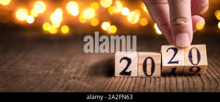 Hand holding wooden cubes calendar with number 2020, happy new year 2020 concept. - Stock Photo