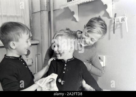 Die Söhne einer kinderreichen Familie waschen sich im Badezimmer, Deutsches Reich 1930er Jahre. Sons of a extended family having a wash in the bathroom, Germany 1930s. - Stock Photo